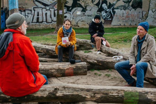 Vier Menschen sitzen auf Baumstämmen zusammen. Sie halten Corona-konformen Abstand. Einer von ihnen ist der Bezirksbürgermeister. Sie nehmen zusammen einen Podcast auf.