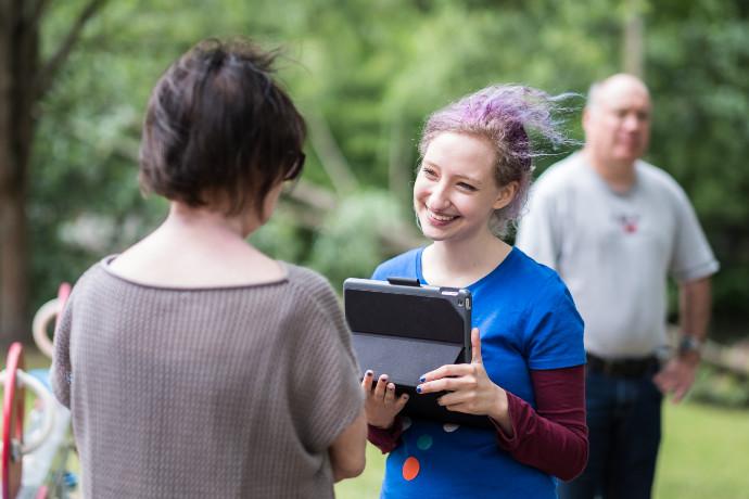 Zwei Menschen treffen sich im freien, eine Frau lächelt und hält ein tablet in der Hand.