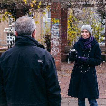 Eine Frau steht einem Mann mit Abstand gegenber. Sie lächelt und hält ein Aufnahmegerät in der Hand