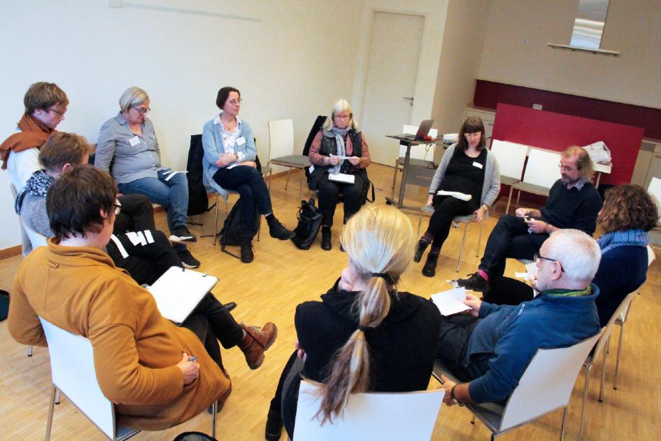 eine Gruppe Senior:innen sitzen zusammen und lesen udn besprechen etwas