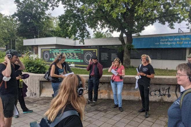 Eine Gruppe von Menschen stehen vor dem Gemeinschaftshaus Langwasser. Die Front des Hauses wurde im Stil eines alten Radios gestaltet. Sie tragen Kopfhörer und starten einen Audiowalk