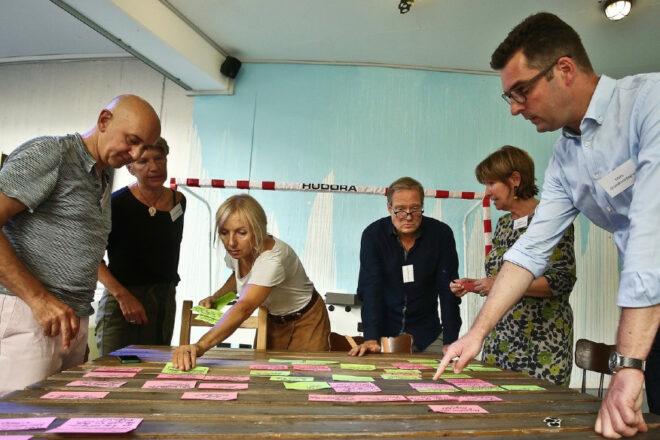 Sechs Leute stehen um einen Tisch, auf dem viele Notizen liegen. Sie diskutieren.