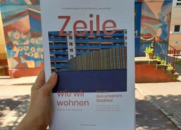 Jemand hält die aktuelle Ausgabe des Stadtmagazins ZEILE in die Kamera