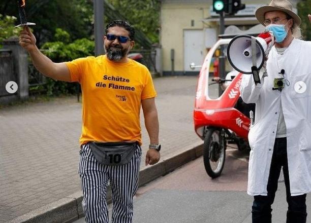 Ein Mann hält eine Fackel in der Hand, er nimmt an einem Fackellaufteil. Neben ihm steht ein Mann mit einem Megaphon
