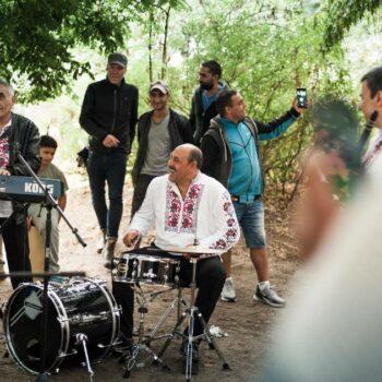 eine Band spielt im Park, einige Leute schauen zu