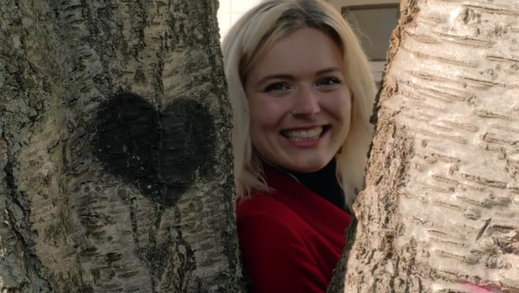 Eine Frau schaut hinter einem Baum hervor, auf den ein Herz gemalt wurde