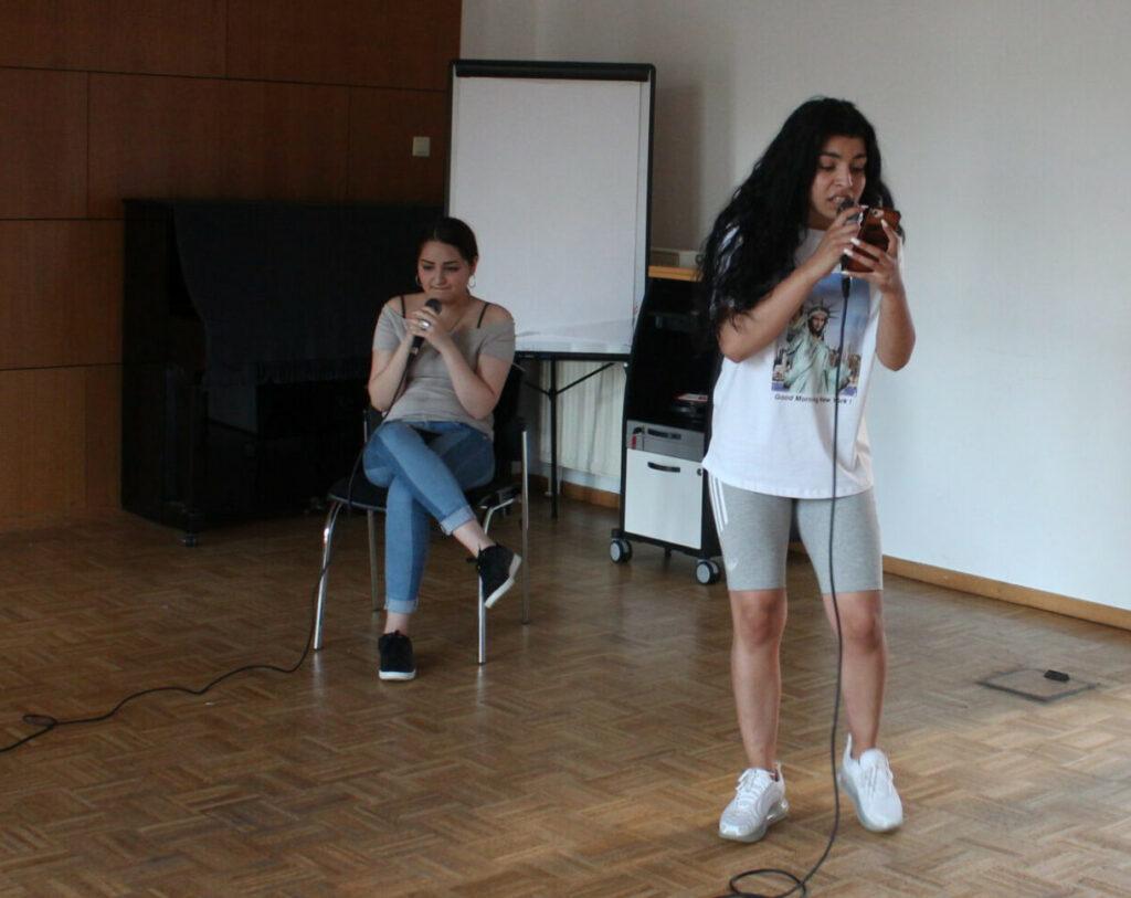 Zwei junge Frauen nehmen einen selbst geschriebenen Rap-Song auf