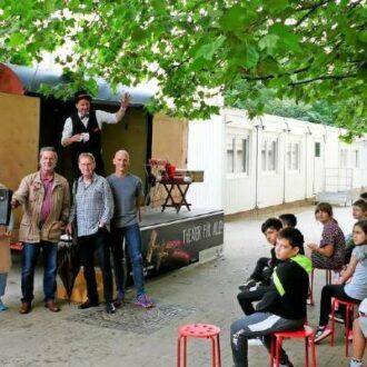 Ein Bauwagen als Zauberbühne steht vor einer Schule. Davor sitzt eine Schulklasse als Publikum
