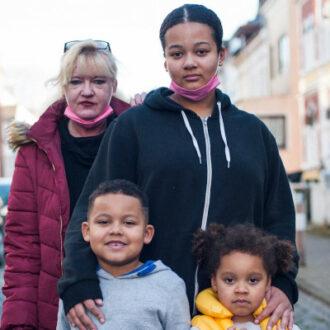 Zwei Frauen unterschiedlicher Herkunft und zwei Kinder stehen auf der Straße und schauen in die Kamera.