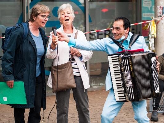 Ein Akkordeonspieler hält zwei Passantinnen ein Mikrofon entegegen und sie singen hinein