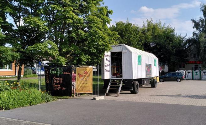 Ein Bauwagen mit geöffneter Tür udn eine Ankündigungstafel stehen auf einem öffentlichen Platz
