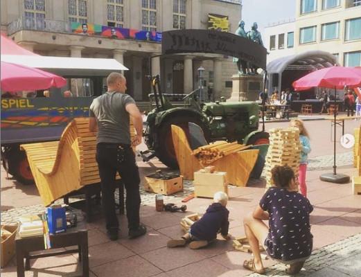 Zwei Erwachsene und zwei Kinder bauen mit Holz große Bänke mitten in der Innenstadt